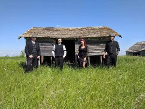 Four band members stand in long grass in front of a decaying building